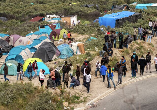 Migrants stand next to tents in the New Jungle in Calais on June 17, 2015 near the ferry port of Calais, northern France