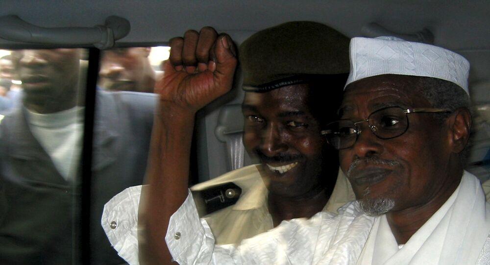 Former Chad President Hissene Habre (R) raises his fist in the air as he leaves a court in Dakar escorted by a Senegalese policeman in this November 25, 2005 file photo
