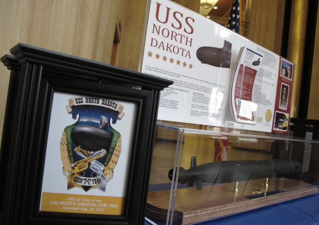 An image of the official crest of the USS North Dakota, left, which is a nuclear attack submarine