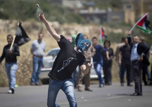 A Palestinian throws a stone at Israeli troops during clashes after a rally marking Nakba Day at Hawara checkpoint near the West Bank city of Nablus.