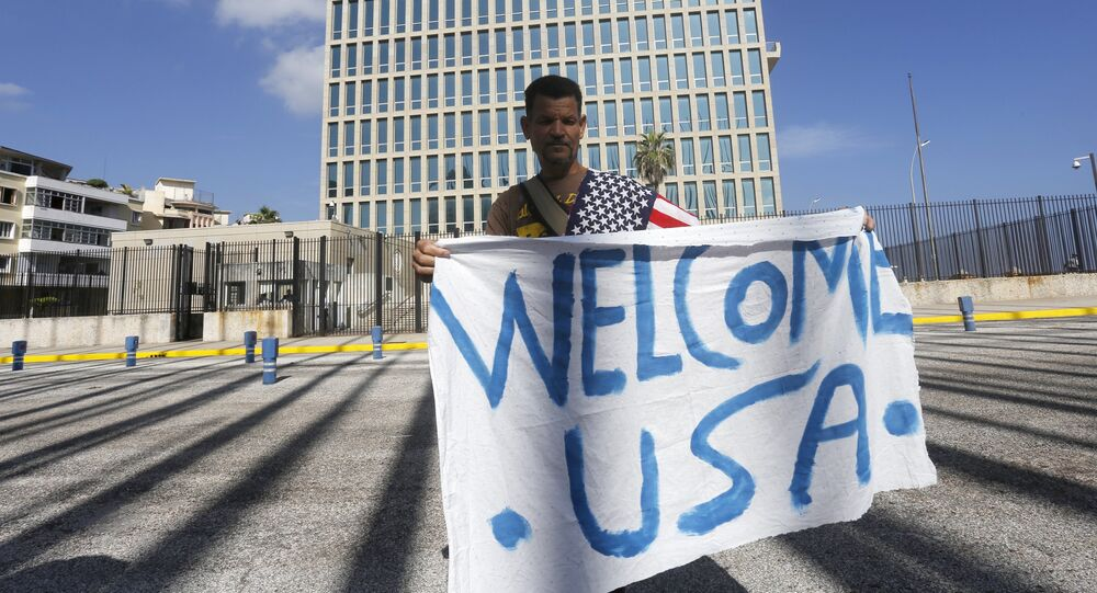 A man hold a banner in front of the U.S. Interests Section in Havana July 20, 2015