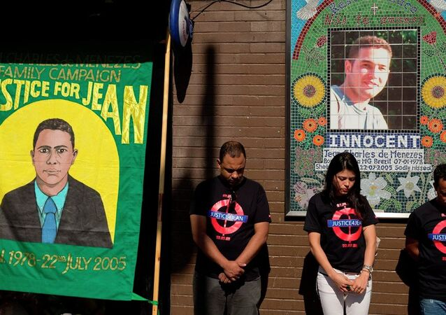 Cousins Alessandro Pereira, right, Vivian Figueiredo and friend Erionaldo da Silva, left, observe a minute's silence on the 10-year-anniversary of the death of 27-year-old Brazilian electrician Jean Charles de Menezes, shot by British police who thought he was a terrorist in the tense aftermath of deadly 2005 London subway bombings, at Stockwell station in London, Wednesday, July 22, 2015.