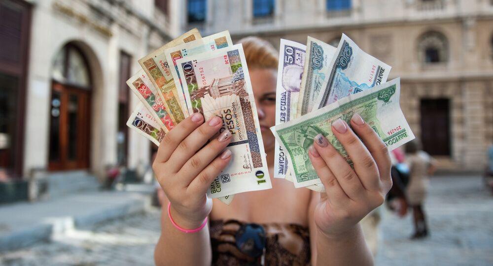 A Cuban shows Cuban Pesos CUP (Left hand) and Convertible Pesos CUC (Right hand)