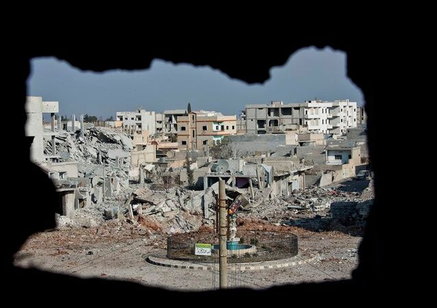 This Nov. 20, 2014 photo shows an area controlled by the Islamic State group, past the Qada Azadi roundabout, foreground, in Kobani, Syria.