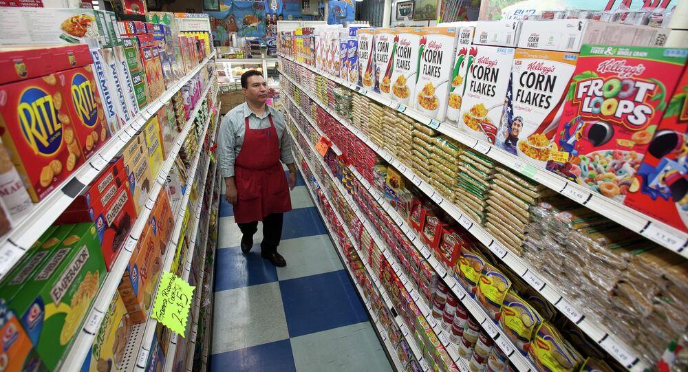 A grocery store employee walks through an aisle.