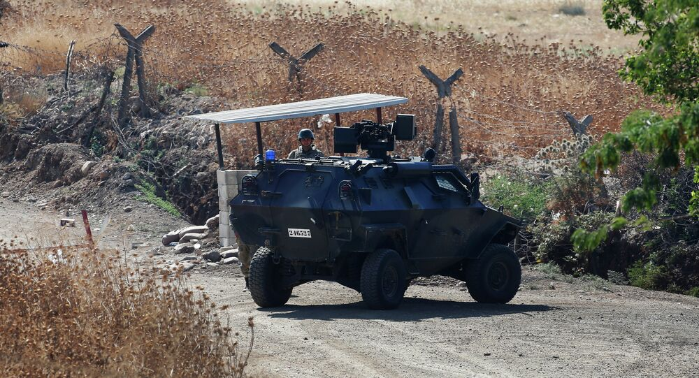 A Turkish soldier stands next to an armoured personnel carrier securing a road near the border with Syria, as seen from the outskirts of the village of Seve, east of the town of Kilis, in southeastern Turkey, Friday, July 24, 2015. Turkish warplanes struck Islamic State group targets across the border in Syria early Friday, government officials said, a day after IS militants fired at a Turkish military outpost, killing a soldier.