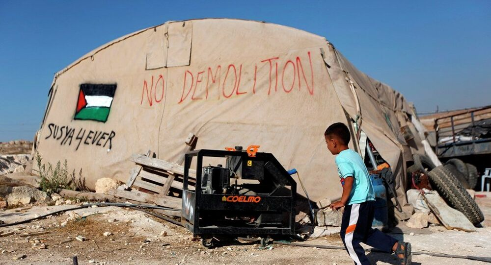 A Palestinian boy runs outside his family tent in the village of Susiya, south of the West Bank city of Hebron.