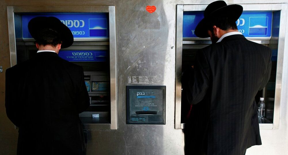 Two Ultra-Orthodox Jewish men take out money from a ATM machine in Jerusalem.
