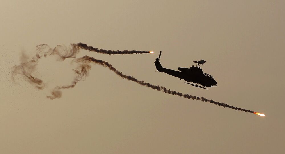 A Cobra attack helicopter fires diversionary flares.