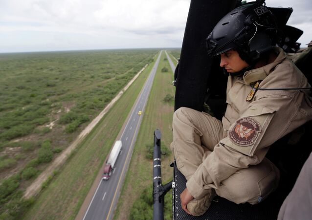 A US Customs and Border Protection Air and Marine agent pears out of the open door of a helicopter during a patrol flight near the Texas-Mexico border.