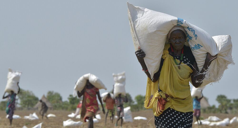 A woman carries a sack of food aid after a food-drop in a field on February 23, 2015 at a village in Nyal, Panyijar county, near the northern border with Sudan