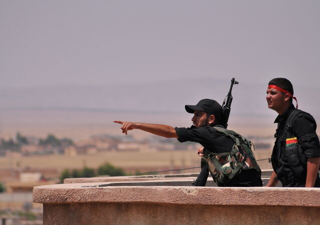 Fighters from the Kurdish People Protection Unit (YPG) monitor the horizon in the northeastern Syrian city of Hasakeh on June 28, 2015