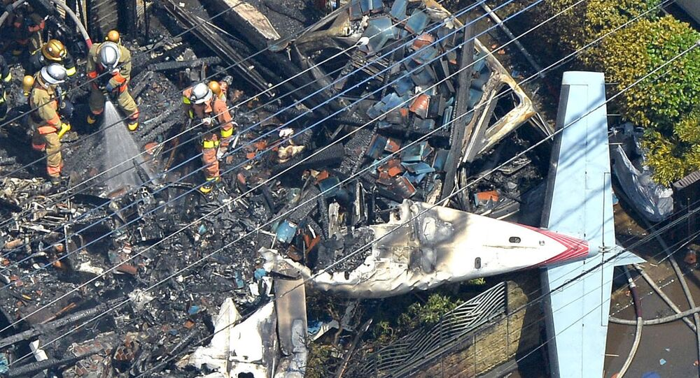 An aerial view shows debris of a crashed light plane and burning house are seen after the plane went down in a residential area and burst into flames, in Chofu, outskirt of Tokyo, in this photo taken by Kyodo July 26, 2015.