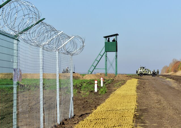 Urkainian border guards stand near an Armoured Personnel Carrier (APCs) parked near a newly constructed part of the border near the Goptivka border crossing on the Urkainian-Russian border, north of Kharkiv, eastern Ukraine, on October 15, 2014
