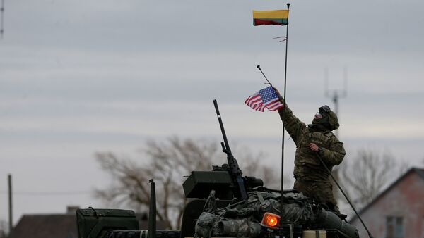 A member of US Army's 2nd Cavalry Regiment raises the US flag on a Stryker vehicle during the ''Dragoon Ride'' military exercise, in Salociai some 178 kms (110 miles) north of the capital Vilnius, Lithuania, Monday, March 23, 2015 - Sputnik International