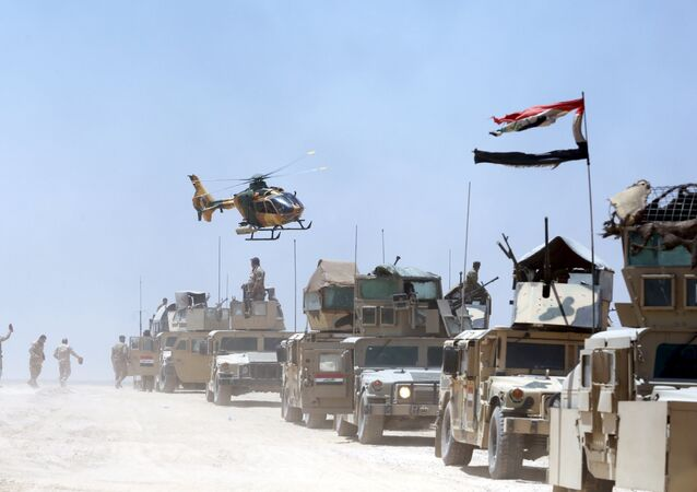 An Iraqi helicopter flies over military vehicles in Husaybah, in Anbar province July 22, 2015