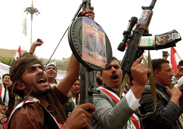 Yemeni protesters hold rifels with portraits of Yemen's former president Ali Abdullah Saleh hung on them during a demonstration against airstrikes carried out by the Saudi-led Arab coalition against Huthi militia in the capital Sanaa on April 3, 2015
