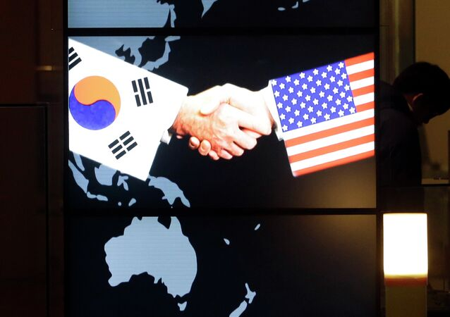 A visitor tour near the screen showing an image of a handshake by the US and South Korean flags at the two countries' security alliance exhibition hall at the Korea War Memorial Museum in Seoul, South Korea
