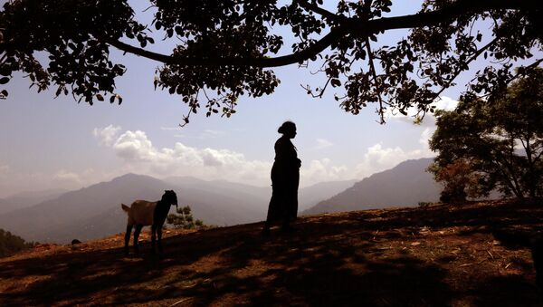 A woman waits for relief material at a Nepalese village - Sputnik International