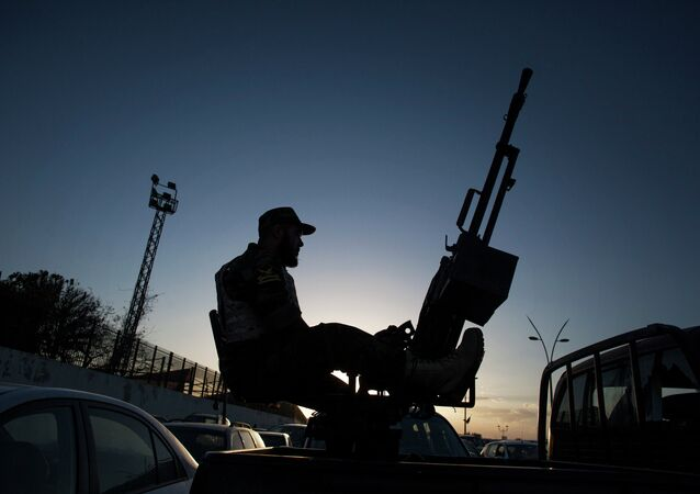 A Libyan army soldier stands guard sitting on an antiaircraft truck during the handover of the Nawaseen military compound, which was the headquarters of Libyan militias, in Souk al-Juma district, Tripoli, Libya