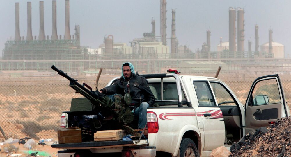 In this March 5, 2011 file photo, an anti-government rebel sits with an anti-aircraft weapon in front an oil refinery, after the capture of the oil town of Ras Lanouf, eastern Libya.