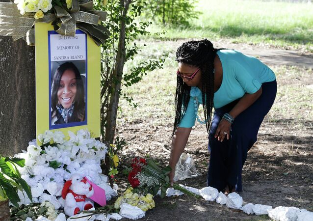 Jeanette Williams places a bouquet of roses at a memorial for Sandra Bland near Prairie View A&M University, Tuesday, July 21, 2015, in Prairie View, Texas