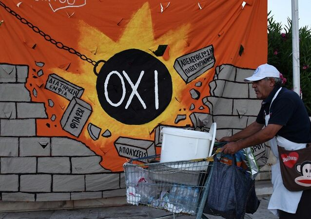 A street vendor pushes his trolley as he passes a banner, depicting a wrecking ball that reads: NO and destroying a wall with anti-austerity measures, in Athens, Wednesday, July 22, 2015.
