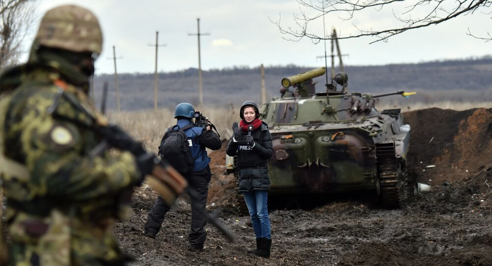 A TV journalist prepares to do a piece to camera in front of an armoured personnel carrier (APC) on the frontline between Ukrainian forces and independent supporters near the eastern Ukrainian city of Debaltseve, in the Donetsk region