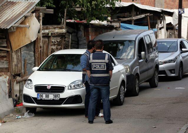 Police officers stand as Turkish police raide homes in Haci Bayram neighborhood in the capital Ankara, Turkey, Monday, July 27, 2015