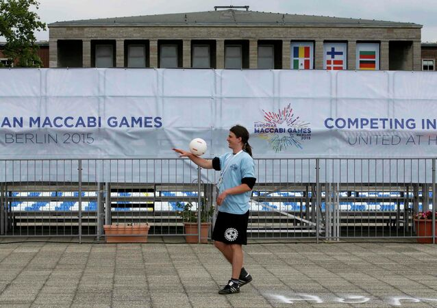 A volunteer plays with a ball outside the Olympic Park during preparations for the 14th European Maccabi Games in Berlin, Germany July 27, 2015.