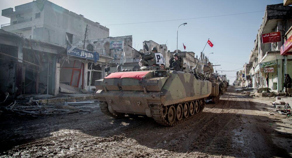 Turkish army vehicles drive in a street of the Syrian town of Kobane (aka Ain al-Arab) on February 22, 2015