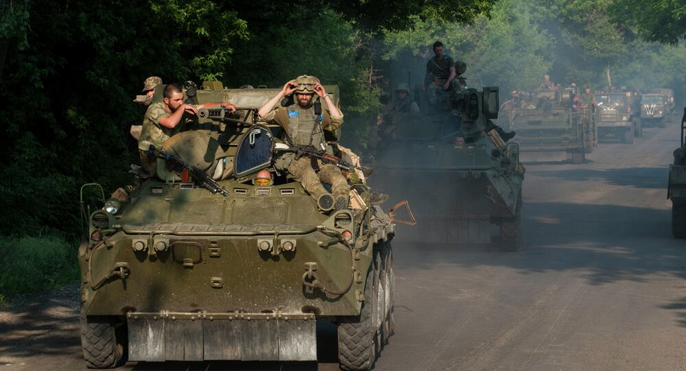 Ukrainian soldiers from the 25th airborne brigade ride atop an APC in a convoy of military vehicles on the outskirts of Marinka, Donetsk region, eastern Ukraine, Thursday, June 4, 2015