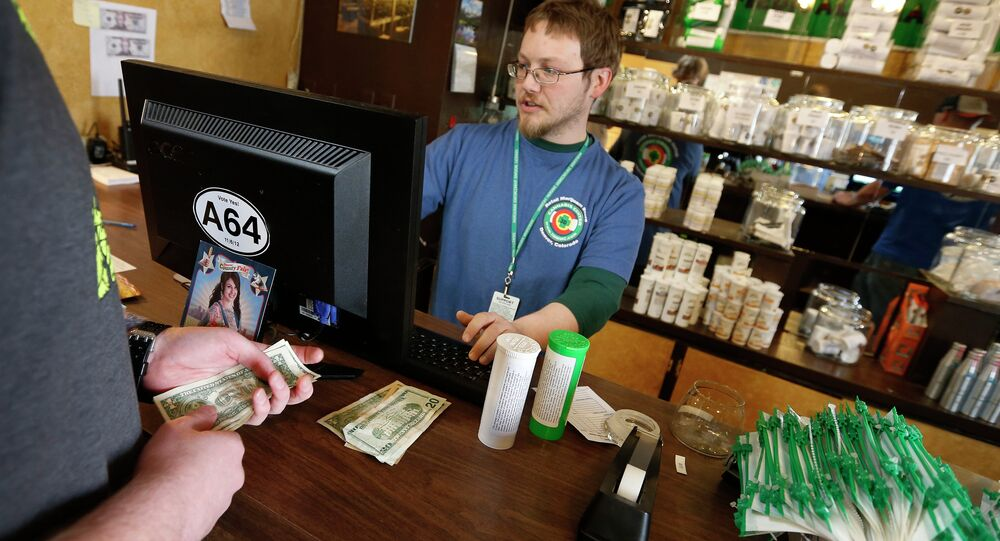 In this May 8, 2014 file photo, a customer pays cash for retail marijuana at 3D Cannabis Center, in Denve