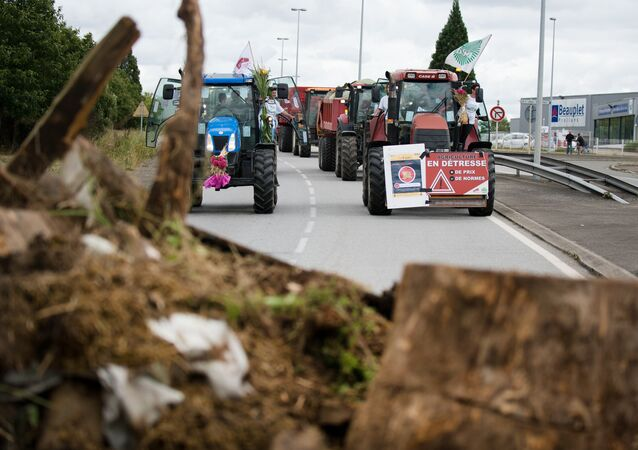 Farmers block the road with tractors, on one of which a placard reads 'Farmers in distress, more prices, less regulation', as they protest near the Lactalis dairy factory during a demonstration against the low sales prices of their production, on July 27, 2015 in Laval, western France