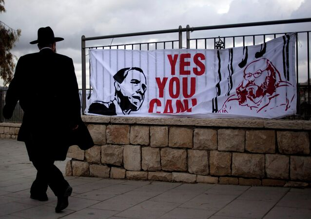 An ultra-Orthodox Jewish man walks past a banner depicting U.S. President Barack Obama, and Jonathan Pollard, a Jewish-American who was jailed for life in 1987 on charges of spying on the United States.