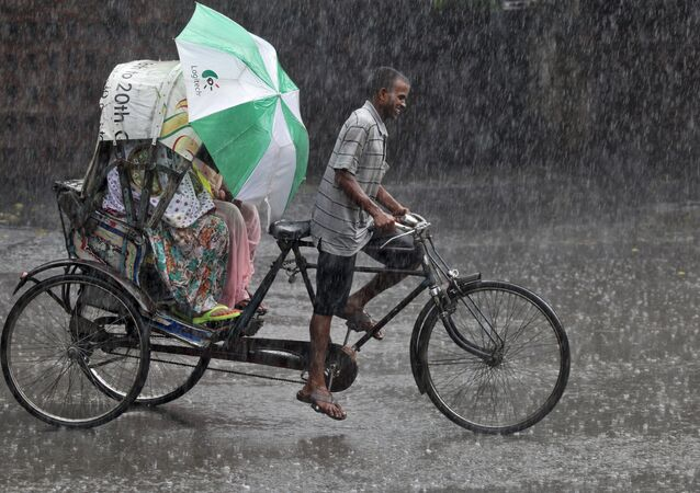 Commuters use an umbrella to protect themselves from a heavy rain shower as they travel in a cycle rickshaw in Chandigarh, India