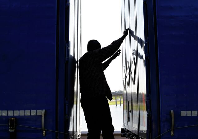 A migrant stands between two trailers of a lorry as he attempts to cross the English Channel,