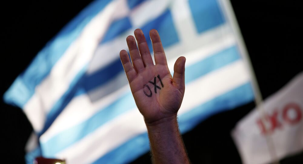 A demonstrator raises his hand with the Greek word ''No'' written on it in front of a Greek flag during a rally in support of the no vote to an upcoming referendum called by Premier Alexis Tsipras on whether to accept the terms of an international bailout, in Athens, in this photo dated Friday, July 3, 2015.