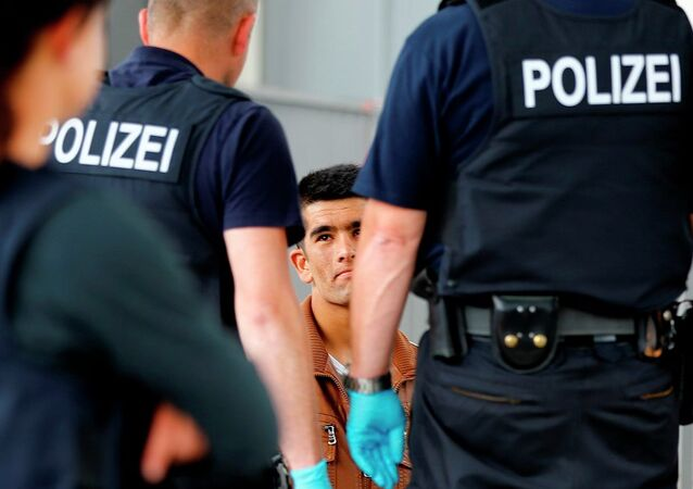 German federal police officers check refugees who arrived without documents at the main station in Rosenheim, Germany, Tuesday, July 28, 2015.