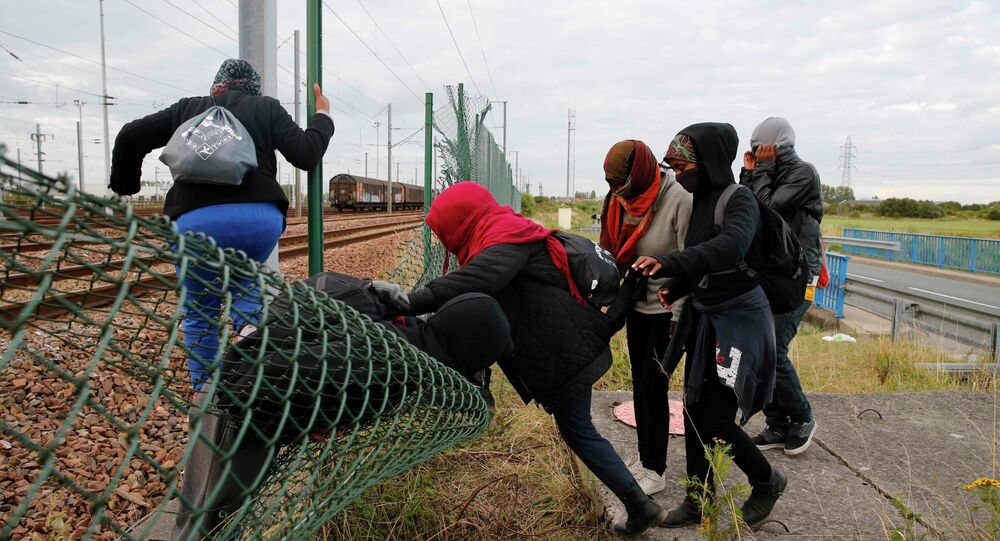 Migrants make their way across a fence near train tracks