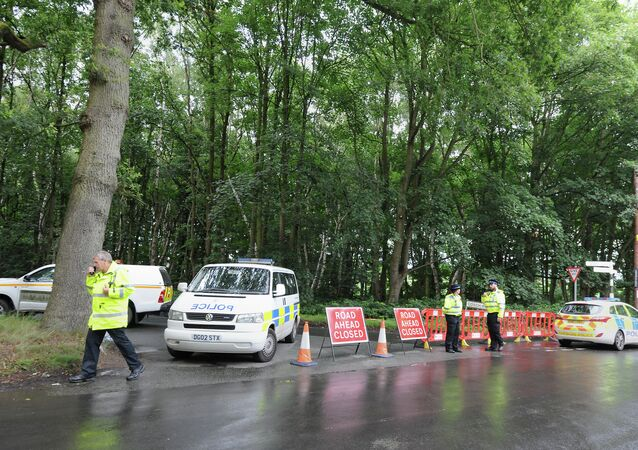 Police stand by a closed road near the scene of a light plane crash, at Oulton Park, in Cheshire, England