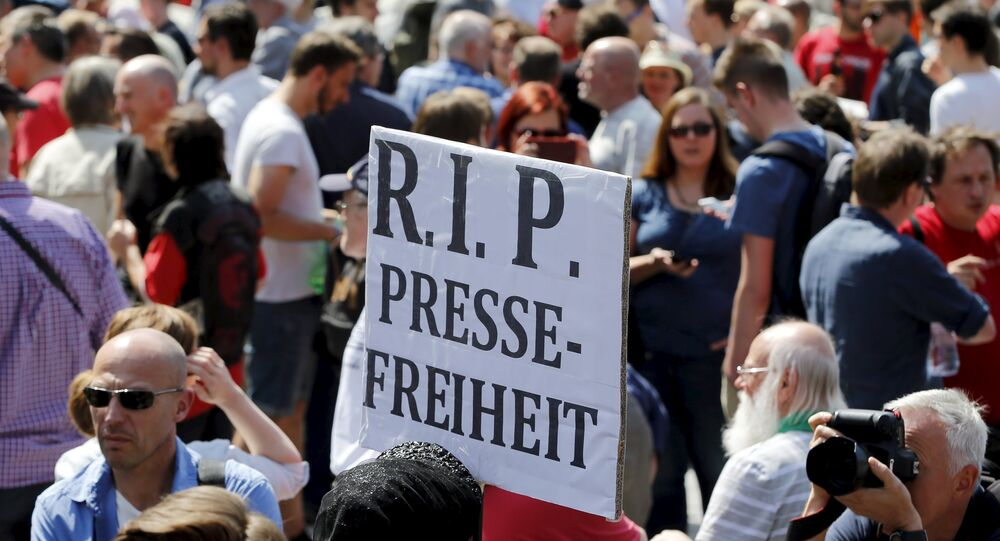 A demonstrator holds up a placard which reads Rest in Peace freedom of press! during a rally to protest against a criminal complaint by the domestic intelligence agency