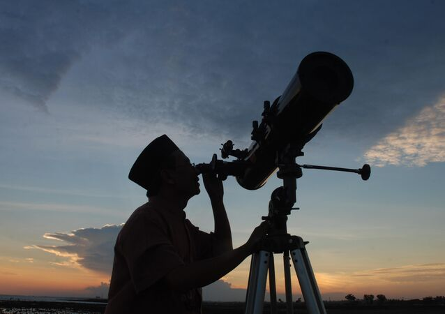 In this photograph taken on August 10, 2010 an official from the State Islamic University (STAIN), uses a telescope to observe the moon after sunset from the coast of Madura in East Java province of Indonesia on the eve of Ramadan