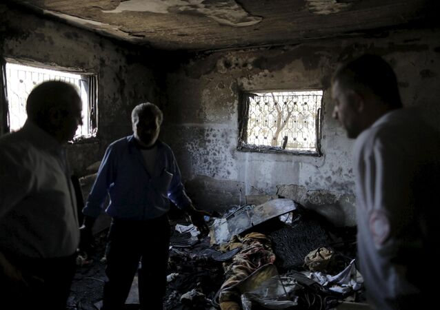 Palestinians inspect a house which was set on fire in a suspected attack by Jewish extremists in Duma village near the West Bank city of Nablus