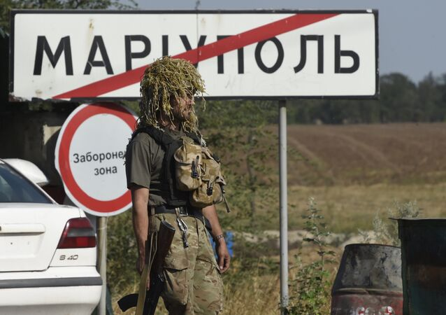 A Ukrainian army soldier walks past a city road sign reading Mariupol on September 4, 2014