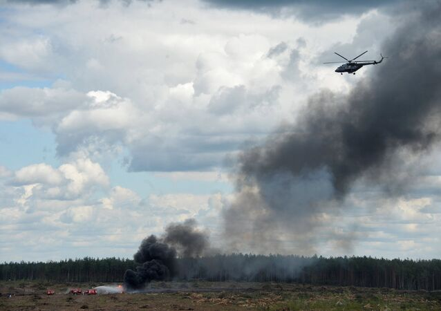 Firefighters extinguish fire at the crash site of a MI-28 helicopter at Dubrovichi base, Ryazan Region