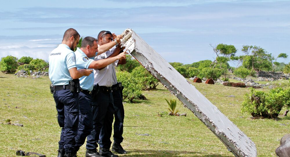 French police officers inspect a piece of debris from a plane in Saint-Andre, Reunion Island
