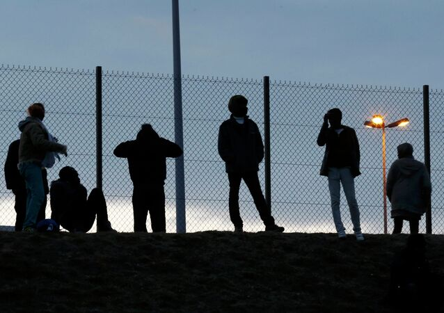 Migrants are seen in silhouette as they stand on a rise near a fence as they gather near the Channel Tunnel access in Frethun, near Calais, France, July 30, 2015