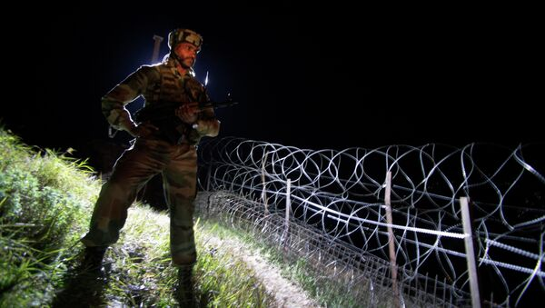 In this Dec. 22, 2013 photo, an Indian army soldier stands guard along barbed wire near the Line of Control (LOC), that divides Kashmir between India and Pakistan, at Krishna Ghati (KG Sector) in Poonch, 290 kilometers (180 miles) from Jammu, India - Sputnik International