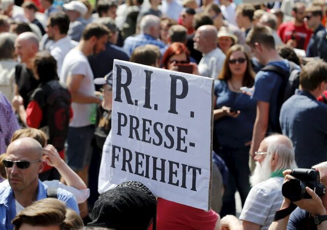 A demonstrator holds up a placard which reads Rest in Peace freedom of press! during a rally to protest against a criminal complaint by the domestic intelligence agency, the Office for the Protection of the Constitution (BfV), over articles about it that appeared on the Netzpolitik.org blog, in Berlin, Germany, August 1, 2015